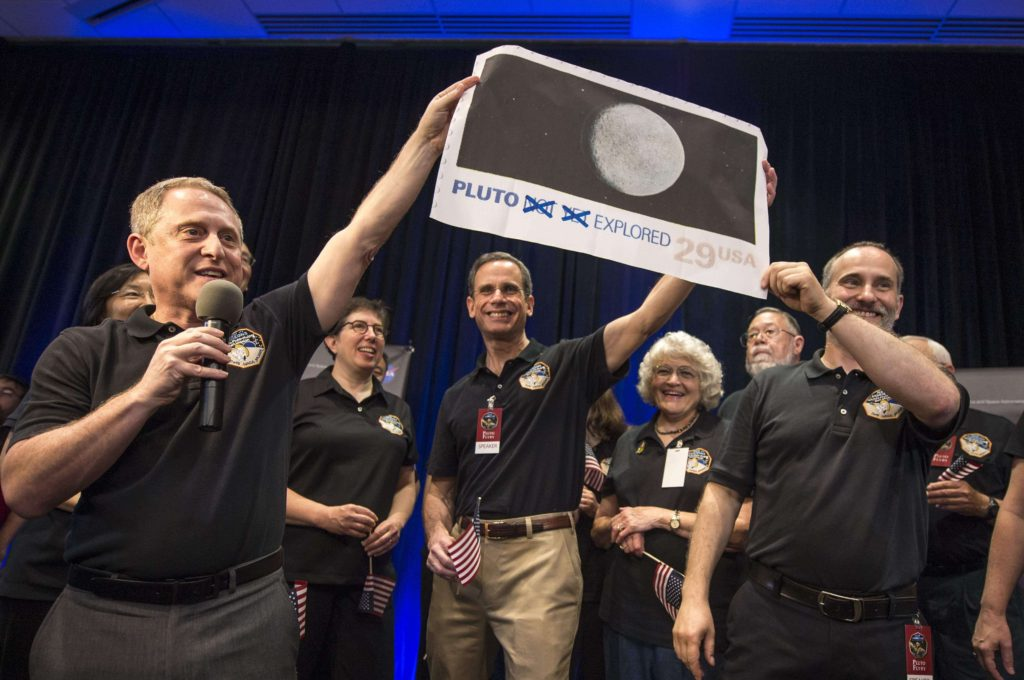 Alan Stern holding the Pluto Stamp